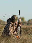 foto of hunt-shotgun  - A young hunter crouching in the grass - JPG