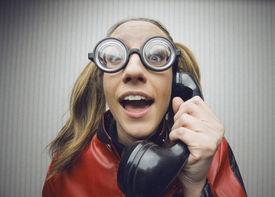 stock photo of nerds  - funny nerd humor woman talking retro vintage black telephone on vintage wallpaper - JPG