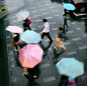 pic of rainy day  - people walking in the street on a rainy day motion blurred - JPG