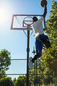 pic of slam  - Young basketball player drives to the hoop with a high flying slam dunk - JPG