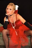 stock photo of harlot  - Beautiful blonde sitting with legs spread dressed up as old time dancing girl or prostitute can also be a sexy mrs - JPG
