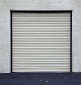 stock photo of roller door  - A Genuine Aluminum Warehouse Garage Roll Up Door and Entrance Door - JPG