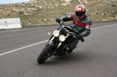 pic of crotch-rocket  - Speeding motorcycle racing around a corner on a country back road - JPG