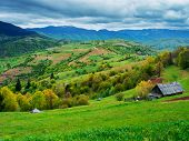 stock photo of mud-hut  - Summer landscape. Green meadow on the slopes with a rural hut.