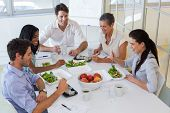 stock photo of half-dressed  - Workers eating fruit and salad together for lunch in the office - JPG