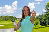 stock photo of ladies golf  - Woman showing a golf ball on the links - JPG