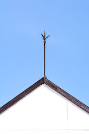 foto of lightning-rod  - Lightning rod on roof top with clear blue sky - JPG