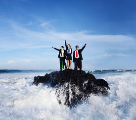 stock photo of gushing  - Three business people wearing superhero costumes posing on a rock with gushing waves - JPG