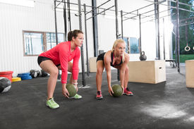 picture of slam  - Young women lift slam balls at crossfit gym center - JPG