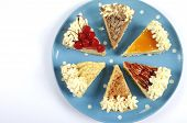 picture of pumpkin pie  - Thanksgiving apple pecan cherry caramel pumpkin spice and chocolate cream cheesecake pie on blue polka dot platter against a white table with copy space - JPG