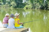 image of dock a pond  - Back view of three children sitting on wooden pier with rod - JPG