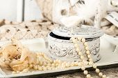 stock photo of vintage jewelry  - antique jewelry box with pearls on ladies dressing table with shabby chic pearl necklace and lace