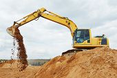 stock photo of construction machine  - excavator machine at excavation earthmoving work in sand quarry - JPG