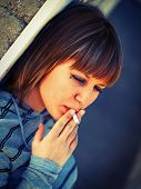 picture of teen smoking  - Teenage girl smoking and leaning on a wall - JPG