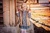 stock photo of country girl  - cute happy child girl playing with fabric easter chicken at country house - JPG