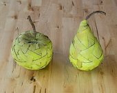 foto of baste  - Green pear and apple made from bast fibre laying on the wooden table