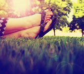 foto of nail paint  - pretty feet on grass at sunset with nails painted and sandals on toned with a retro vintage instagram filter  - JPG