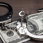 stock photo of handcuff  - handcuffs and one hundred dollars on the wooden table - JPG