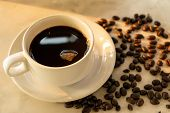 image of latte coffee  - Coffee cup and coffee beans on marble table.