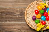 stock photo of nest-egg  - Easter nest with colorful eggs and yellow daffodils on a wooden table - JPG