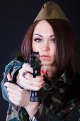 stock photo of cap gun  - Young woman in the military uniform with the gun over black background - JPG