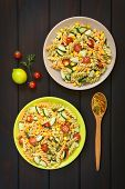 pic of sweet-corn  - Overhead shot of two plates of vegetarian pasta salad made of tricolor fusilli sweet corn cucumber and cherry tomato photographed on dark wood with natural light - JPG