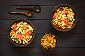 image of sweet-corn  - Overhead shot of two rustic bowls of pasta salad made of tricolor fusilli sweet corn cucumber cherry tomato and sausage photographed on dark wood with natural light - JPG