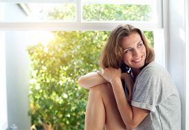 picture of mature adult  - Portrait of a happy mid adult woman sitting by window at home - JPG