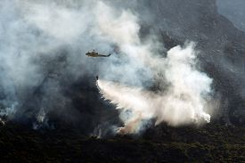 picture of helicopters  - Fire fighting helicopter dropping water on a fire on a mountain late afternoon