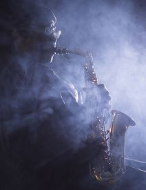 foto of saxophone player  - African American jazz musician playing the saxophone through smokey light in club