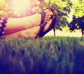 stock photo of painted toes  - pretty feet on grass at sunset with nails painted and sandals on toned with a retro vintage instagram filter  - JPG