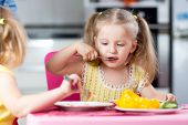 pic of daycare  - Little children eating food at daycare or at home  - JPG