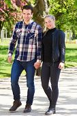 foto of stroll  - Attractive trendy couple enjoying a walk in the park strolling along a paved walkway hand in hand smiling at the camera - JPG