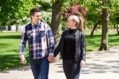 image of stroll  - Affectionate couple strolling hand in hand through a park as they enjoy the warm sunshine smiling and chatting together as they walk along - JPG