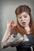 picture of stinky  - Cute girl holds up two smelly stinky sneaker shoes - JPG