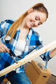 foto of enthusiastic  - Woman assembling wooden furniture using screwdriver - JPG