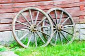 picture of wagon wheel  - Two wooden wagon wheels leaning against old farm house - JPG
