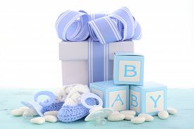 stock photo of teething baby  - Baby shower Its a Boy blue gift with gift box baby booties and dummy on pale blue shabby chic rustic wood table - JPG