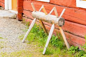 picture of peg-leg  - Old antique sawhorse in traditional style outside a red farm house - JPG
