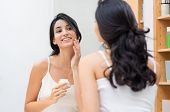 Woman caring of her beautiful skin on the face standing near mirror in the bathroom. Young woman app poster