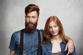 Beautiful Young Caucasian Couple Posing Indoors. Handsome Stylish Man With Fuzzy Beard Hugging His A poster
