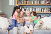 Grandchildren playing with grandparents at home poster