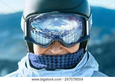 poster of Close Up Of The Ski Goggles Of A Man With The Reflection Of Snowed Mountains.  A Mountain Range Refl
