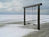 Cold Snap - Two Swing Hang On A Wooden Beam In The Middle Of The Lonely Beach In Winter. The Sand Is poster