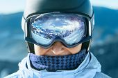 Close Up Of The Ski Goggles Of A Man With The Reflection Of Snowed Mountains.  A Mountain Range Refl poster