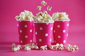 Tasty popcorn falling into cups on pink background. Salty fresh crusty homemade popcorn in pink pape poster