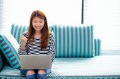 Beautiful Of Portrait Asian Young Woman Excited And Glad Of Success With Laptop On Sofa At Living Ro poster