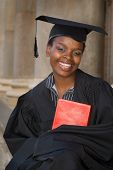 pic of academia  - African American college student graduating with mortarboard and book - JPG