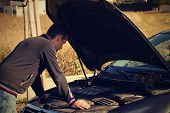 A Young Man Is Standing By A Broken Car And Looks Under The Car Hood.a Young Man And Broken  Car On  poster