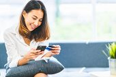 Young Beautiful Asian Woman Using Smartphone And Credit Card For Online Shopping At Home With Copy S poster